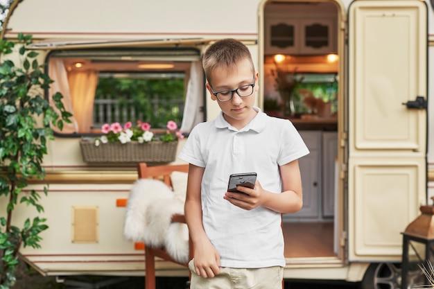 車輪の家の近くの夏の休暇に携帯電話を持つ子供男の子 Premium写真