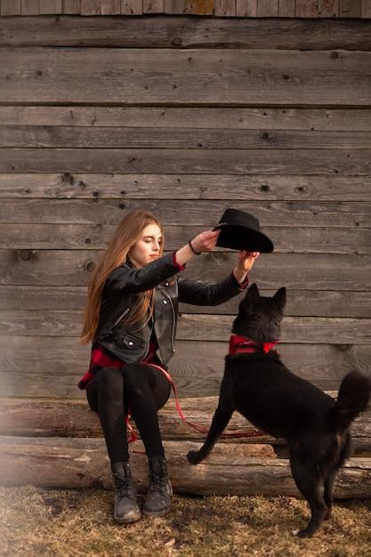 彼女の黒い犬と遊んで幸せな若い女 Premium写真