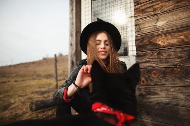 少女は彼女の黒い犬を養う Premium写真