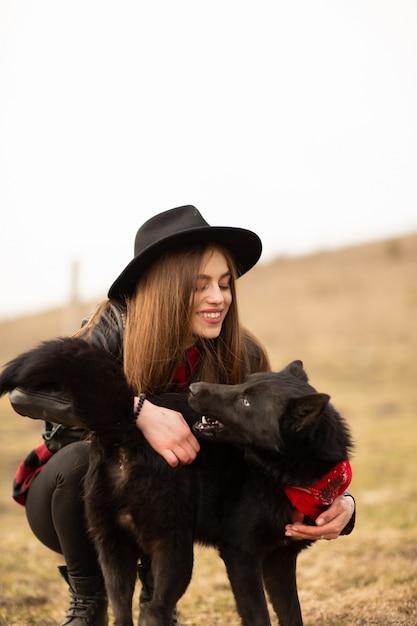 黒い帽子を持つ幸せな若い女 Premium写真