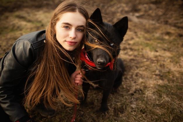 カラフルな目をした少女と彼女の犬の素晴らしい肖像画。 Premium写真