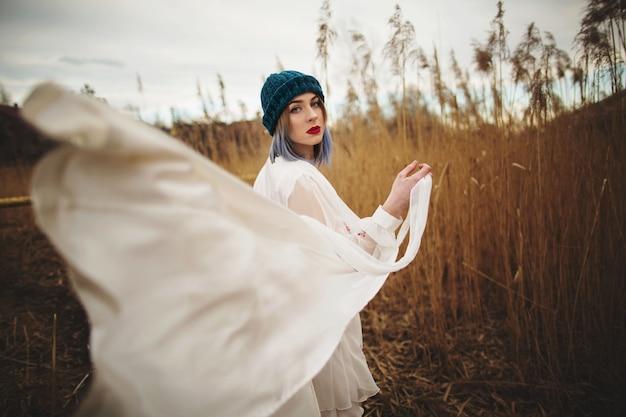 スタイリッシュな帽子と麦畑を歩いて白いドレスの少女 Premium写真