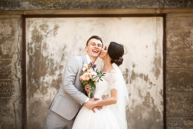 美しい結婚式のカップルが古い壁の近くにキス Premium写真