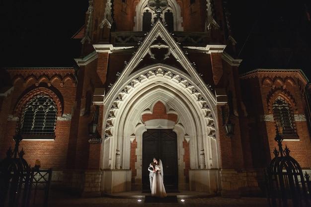 クラクフ、新婚夫婦の結婚式のカップルの夜のフォトセッションは、教会を散歩します。 Premium写真