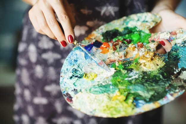 Руки женщины держа кисть и палитру с масляными красками. закройте концепция искусства Premium Фотографии