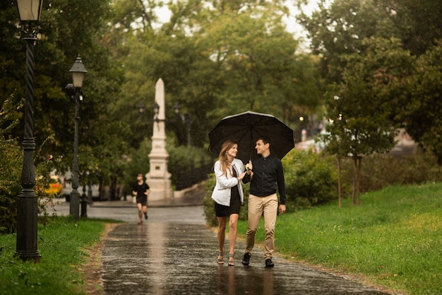 雨の日に公園を歩いている若いカップル。ブダペストのラブストーリー Premium写真