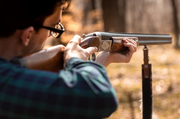 Осенний охотничий сезон. человек охотник с ружьем. охота в лесу Premium Фотографии