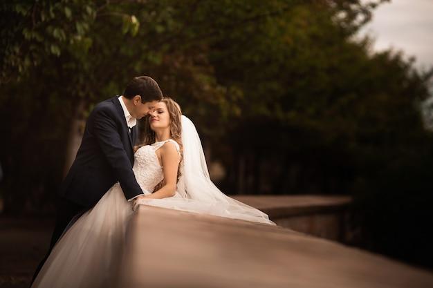 Свадебный снимок жениха и невесты в парке. романтическая сцена в парке Premium Фотографии