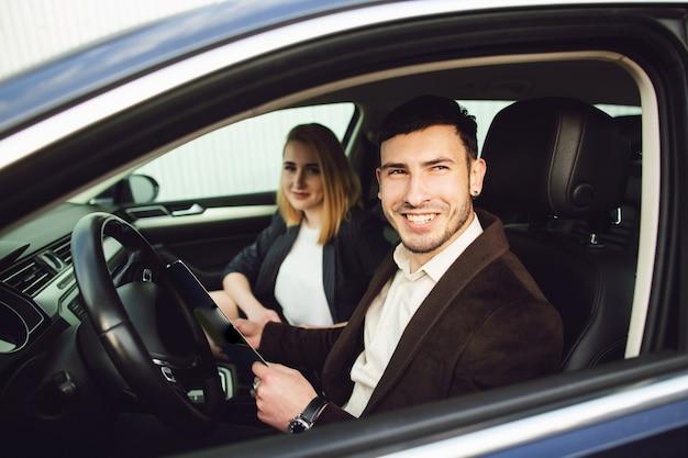 若い男が車を借ります。ディーラーセンターの従業員が車の中で書類を見せています Premium写真