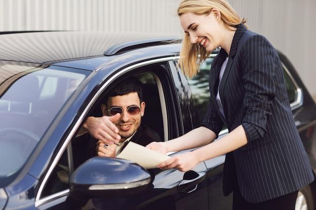 若い男が車を借ります。ディーラーセンターの従業員が車の近くに書類を見せています Premium写真