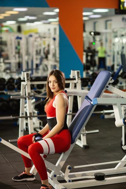 毎日のスポーツ。ジムでワークアウト若い健康な女性。シミュレーターで演習を行う Premium写真