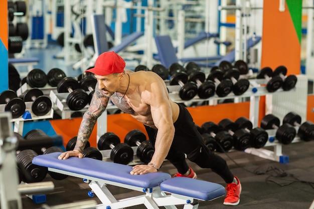 ジムでのトレーニング中にベンチで腕立て伏せを行う強いスポーティな男 Premium写真