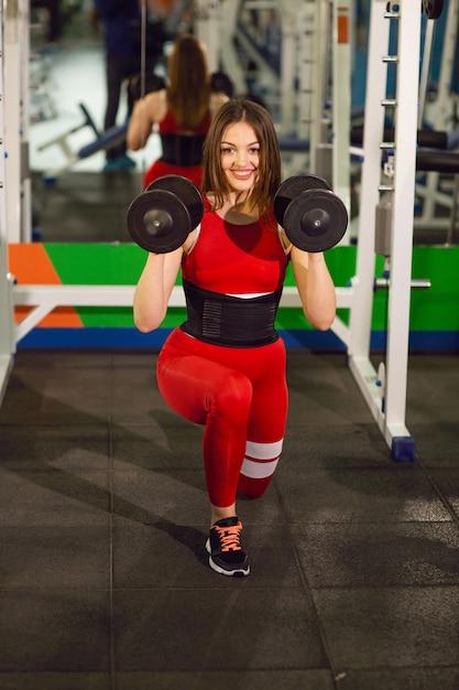 ジムでダンベルでのエクササイズの若い美しい女性。喜んで笑顔の女の子は彼女のトレーニングプロセスで楽しんでいます。 Premium写真