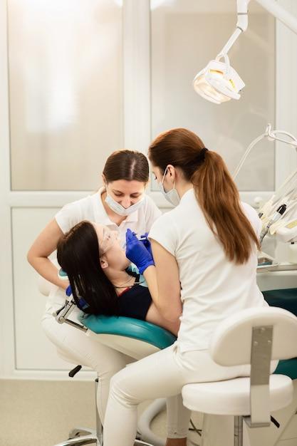 医者の聖霊降臨祭のアシスタントは、患者の歯を治療し、虫歯を防ぎます。口腔病学のコンセプト Premium写真