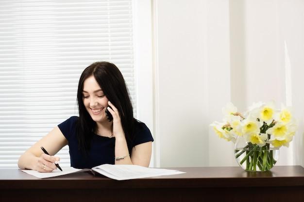 Красивая девушка на рецепции, отвечая на звонок в стоматологическом кабинете Premium Фотографии