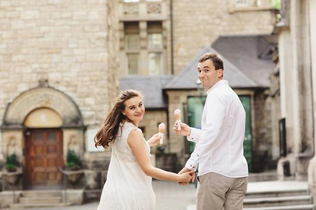 妊娠中の女性のドレスと彼女の夫は街を歩いています。 Premium写真