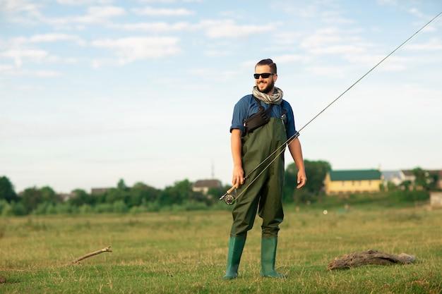 特別なスーツと釣り竿を持つ幸せな漁師 Premium写真