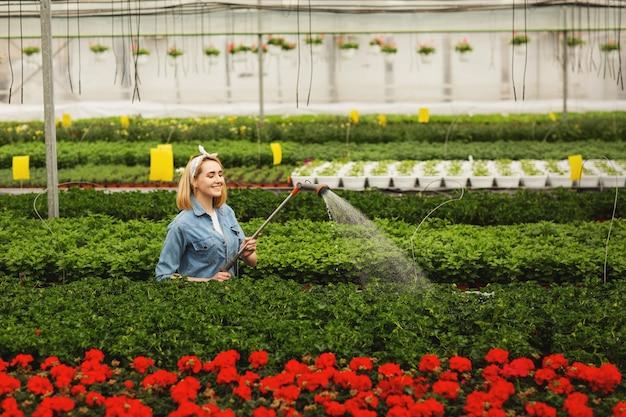 オランジェリーに立っていると植物に水をまく笑顔の美しい若い女性 Premium写真