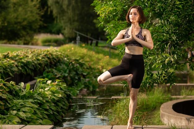 公園の装飾的な湖の近くの橋でヨガの練習の若い女性 Premium写真