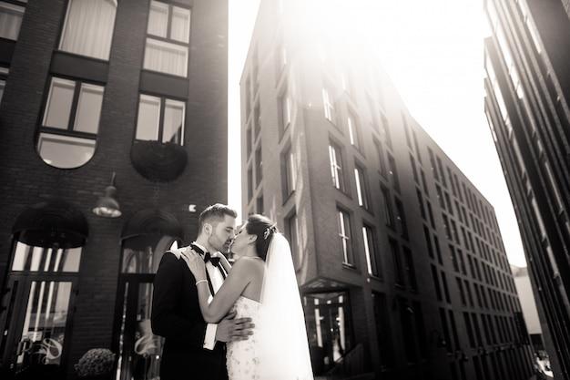Жених и невеста гуляют по городу, день свадьбы, брак. жених и невеста в городских. молодая пара в день свадьбы. Premium Фотографии