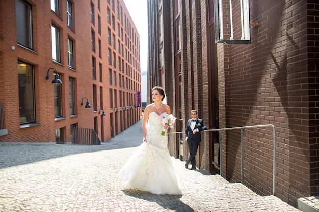 街を歩いて新郎新婦、結婚式の日、結婚。都市の新郎新婦。結婚式の日の若いカップル。 Premium写真