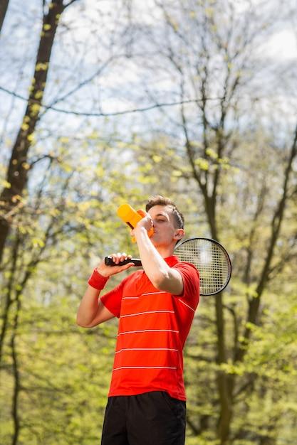 Мужчина в красной майке позирует с теннисной ракеткой и питьевой водой из термопары. концепция спорта Premium Фотографии