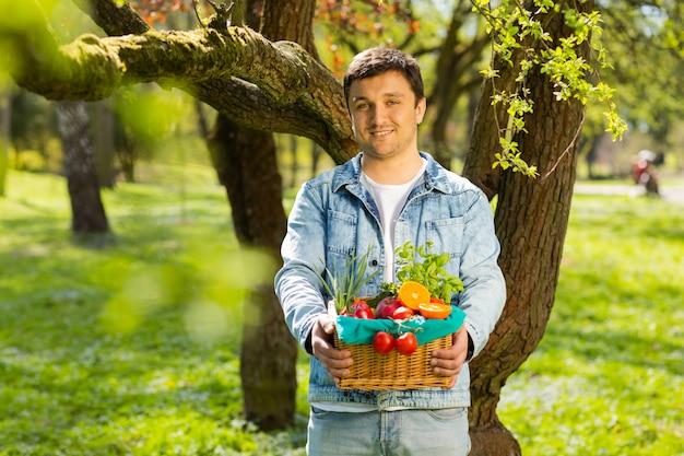自然の農家の背景の手の中の野菜と果物のバスケット Premium写真