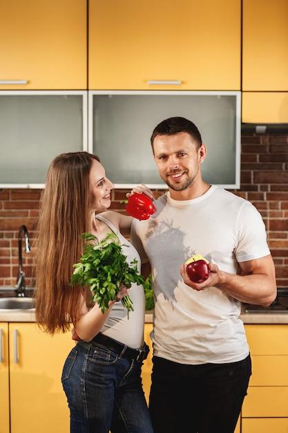 キッチンに立っている若い魅力的なカップル。男と女の野菜や果物を保持しています。健康食品のコンセプトです。家族のための食事療法、健康的なライフスタイル Premium写真