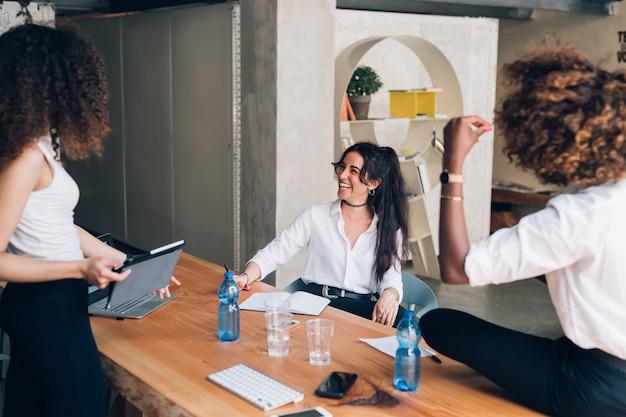 共同作業オフィスで会議を持つ若い多文化実業家 Premium写真