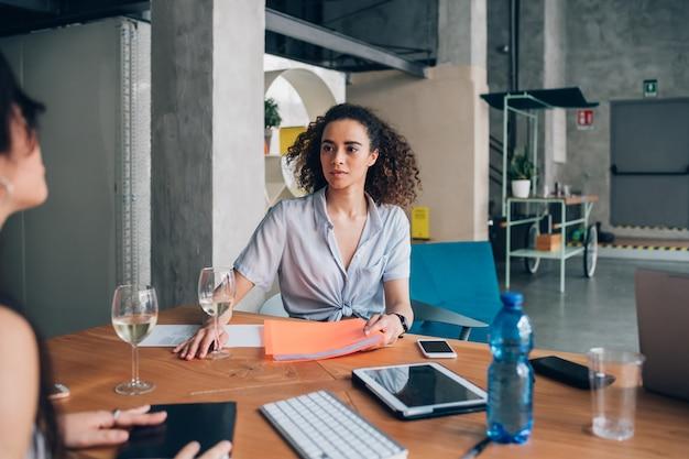タブレットで座っている若い巻き毛の女性 Premium写真