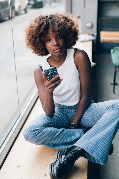 カメラを探しているスマートフォンを持つ若い黒人女性 Premium写真