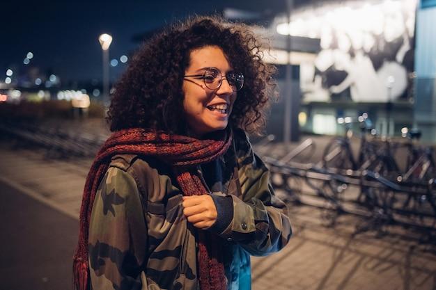 通りで笑っている巻き毛のブルネットの少女 Premium写真