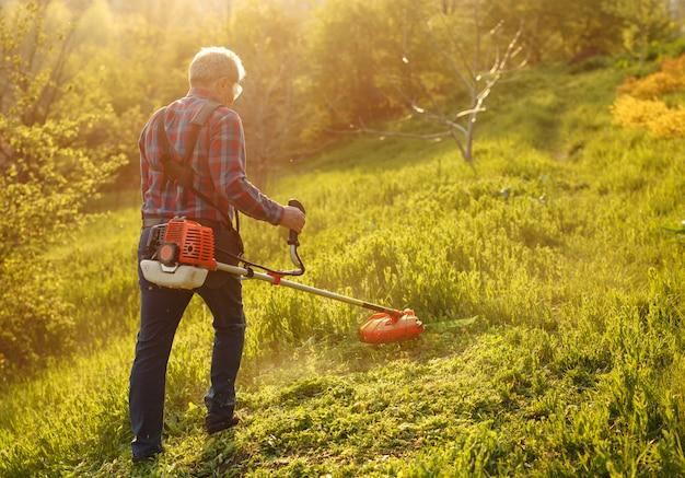 刈り取りトリマー - 日没時の緑の庭で草を刈る労働者。 Premium写真