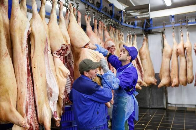 肉の製造で肉屋の豚肉を切断します。 Premium写真