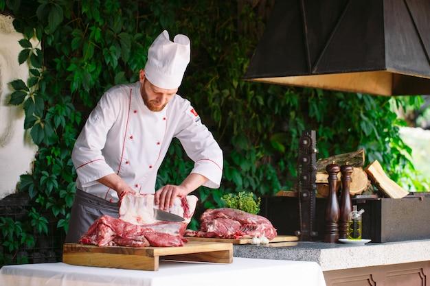 Мужчина-повар режет мясо ножом в ресторане. Premium Фотографии