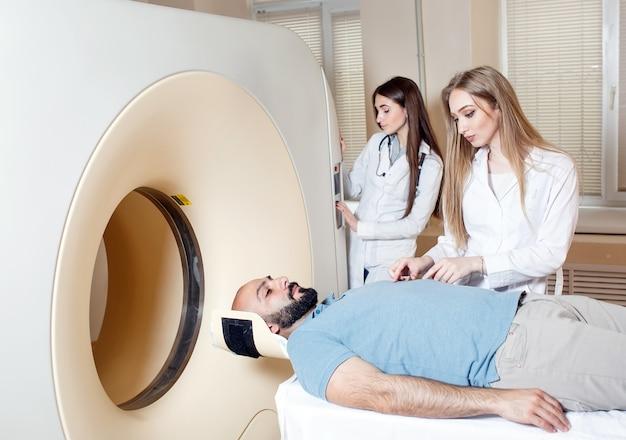 Счастливый пациент проходит сканирование мрт в больнице. Premium Фотографии