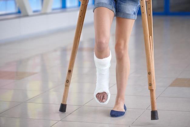 若い女の子が病院の廊下で松葉杖に乗っています。 Premium写真