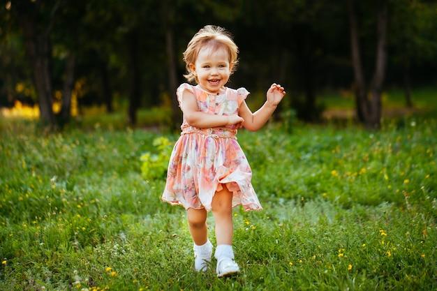 公園の芝生の上を実行している幸せなかわいい女の子。幸福。 Premium写真