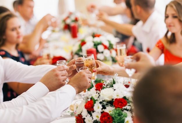 ホリデーイベントの人々がシャンパンでお互いを応援します。 Premium写真