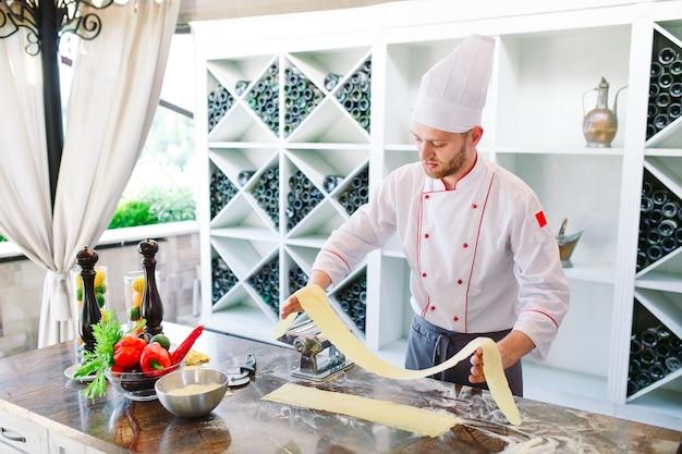 Шеф-повар готовит пасту для посетителей. Premium Фотографии