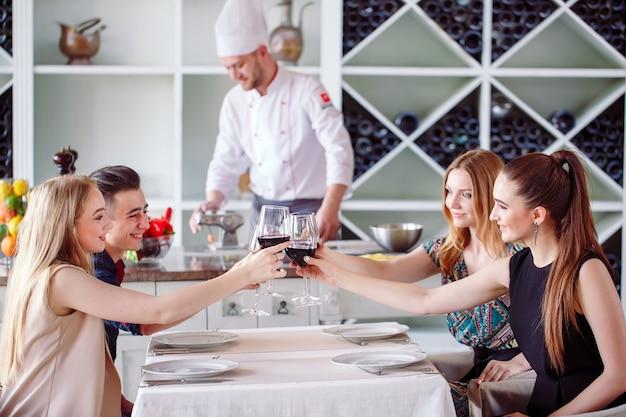 コックが準備するバックグラウンドでワインを飲むレストランの若者。 Premium写真