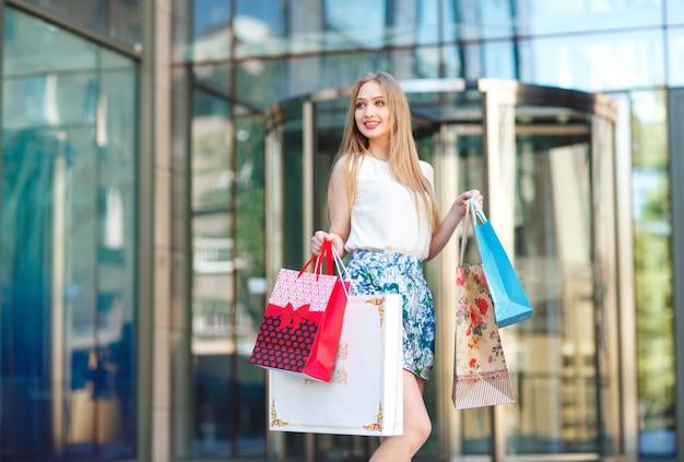 ライフスタイル肖像若いブロンドの女の子、ショップから出て行く買い物袋。 Premium写真
