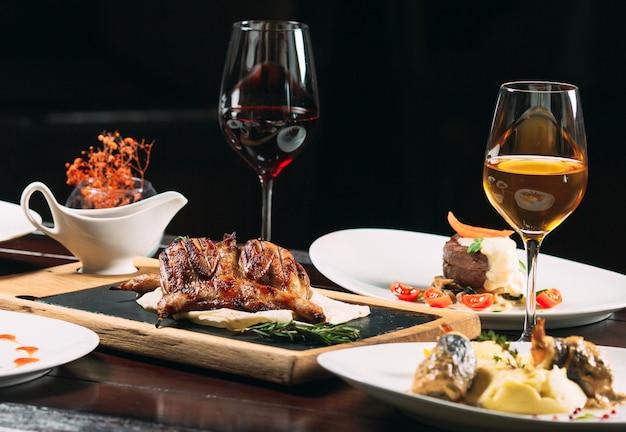 焼きヤマウズラ、スズキ、タルタル。レストランのテーブルの上のさまざまな料理。 Premium写真