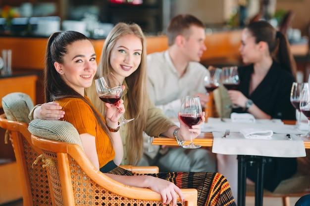 友人はレストランでワインを飲んだり、話したり、笑顔を楽しんでいます。 Premium写真