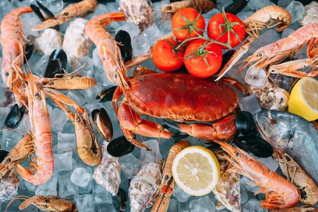 氷の上でシーフード。カニ、チョウザメ、貝、エビ、ラパナ、ドラド、ホワイトアイス。 Premium写真