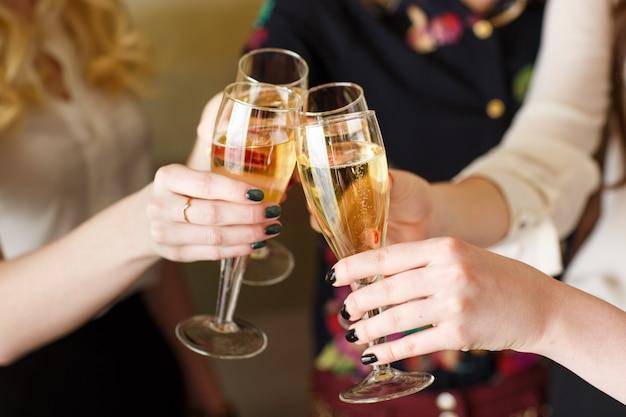 乾杯のシャンパンのグラスを保持手 Premium写真