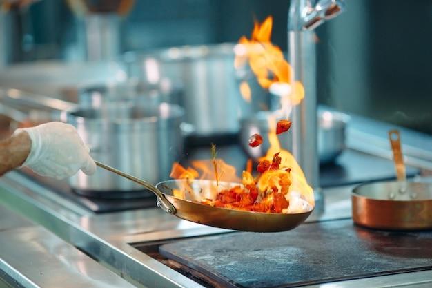 鍋に野菜を調理するシェフ。 Premium写真