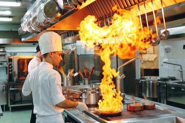 モダンなキッチン料理人はレストランやホテルのキッチンのコンロで食事を用意します。 Premium写真