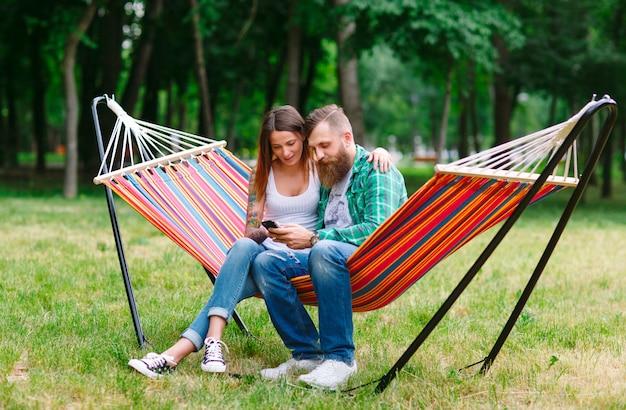 ハンモックの上に座って携帯電話と若いカップル Premium写真