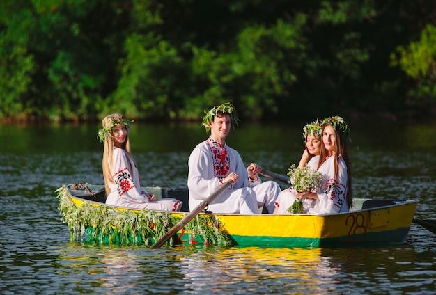 Середина лета. группа молодых людей в национальных костюмах плывет в лодке, украшенной листьями и наростами. славянский праздник ивана купалы. Premium Фотографии